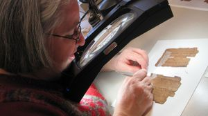 Conservator Myriam Krutzsch removes tape from a fragment during a visit to U-M